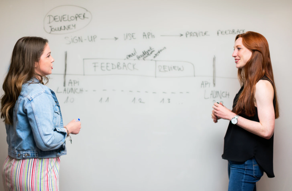 professors at the university of calgary, two women standing in front of white board