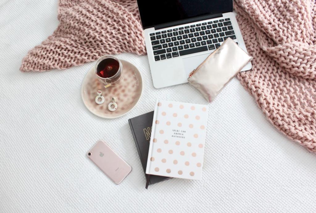 residences pink blanket, phone, laptop on bed