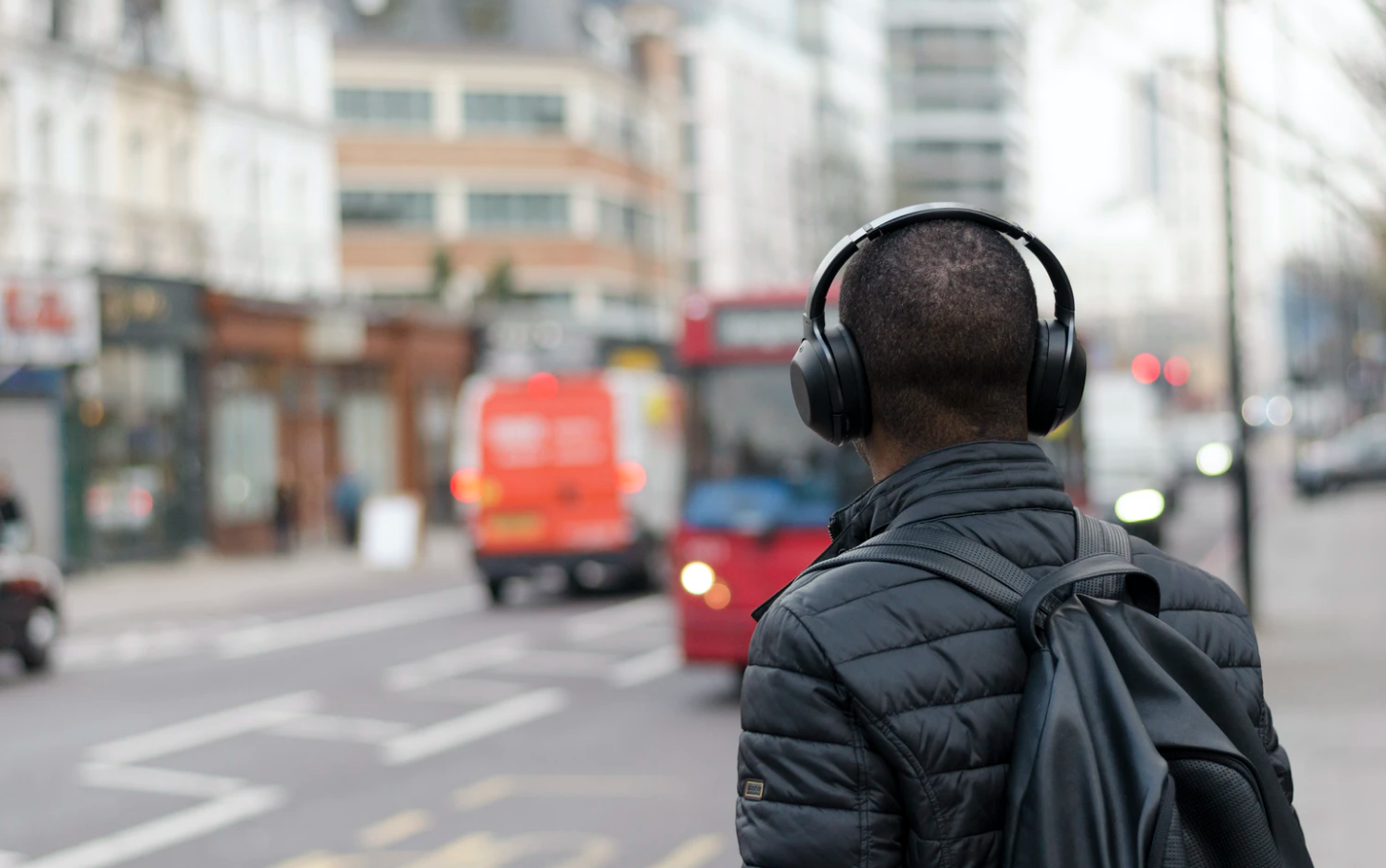 commute etiquette student wearing headphones waiting for bus
