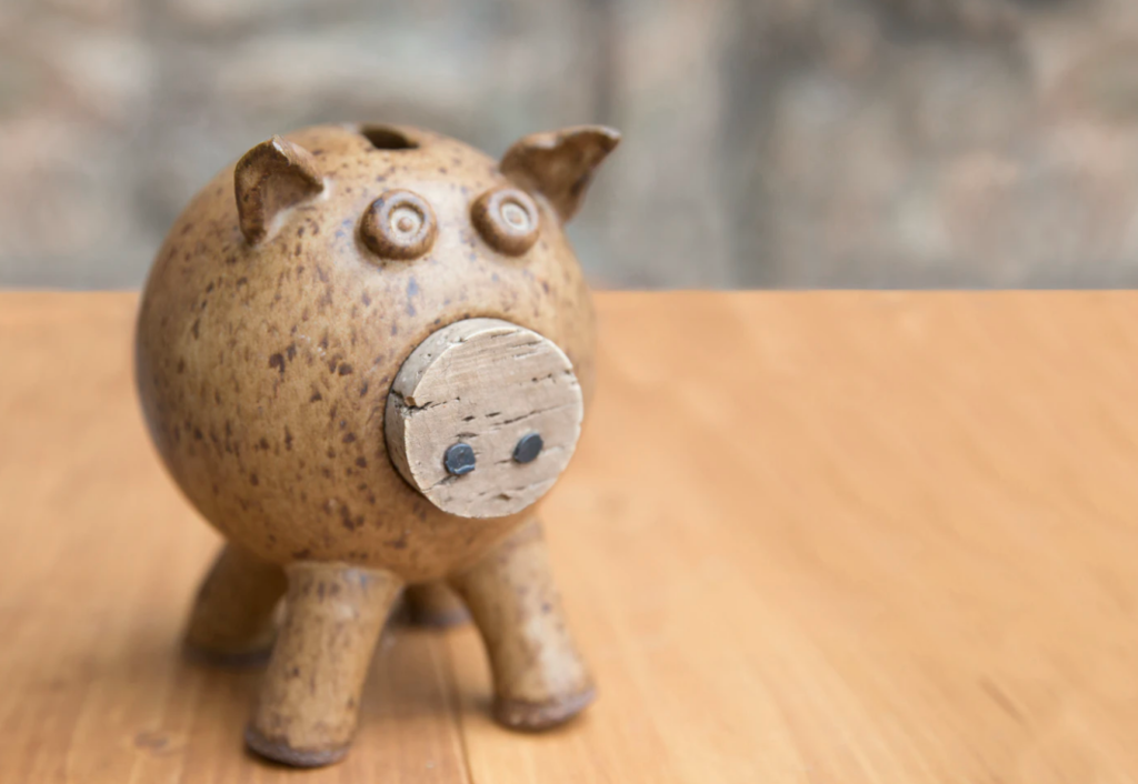 brown piggybank on wooden table holland college financial aid