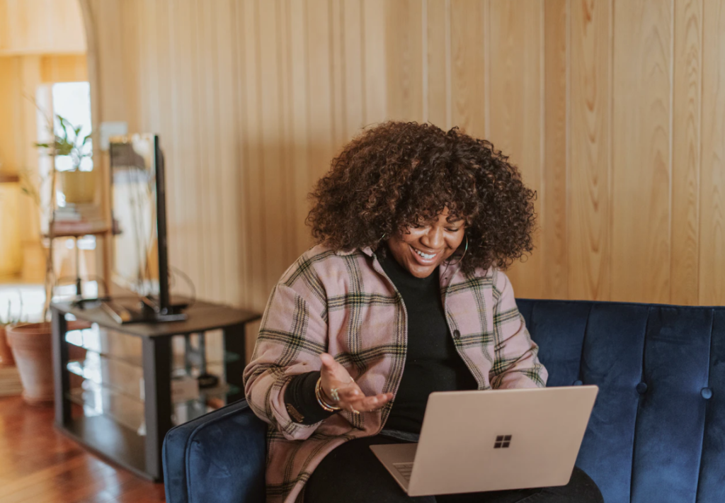 financial assistance at ryerson university , woman wearing a plaid jacket is smiling down at her open laptop resting on her legs