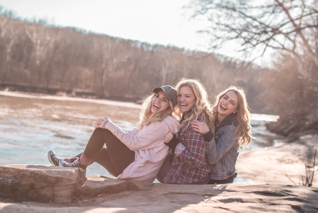 studying at waterloo , group of blonde teenagers sitting on rock leaning against one another and laughing